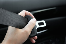 Woman Holding A Buckle Of A Safety Belt In Hand And Fastening A Seatbelt, Car Safety And Driver Protection Concept