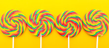 Halloween Trick Or Treat Social Media Web Banner. Bright Rainbow Lollipop Candy On Colorful Yellow Wood Table For Halloween Trick Or Treat Or Childrens Party.