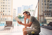 Young Man With Headphone Near Swimming Pool Reading Book