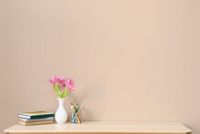 Stylish Workplace With Beautiful Flowers, Notebooks And Pen Holder Near Color Wall