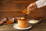 Woman pouring honey onto plate with tasty pancakes on wooden background