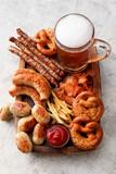 Mug of cold beer, wooden board with Bavarian sausages and snacks on light background. Oktoberfest celebration