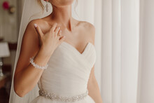 Exciting Moment Of Waiting For Groom, Wedding Day, Unrecognizable Bride Looking Out Window. Concept Of Bride's Gathering For Celebration.