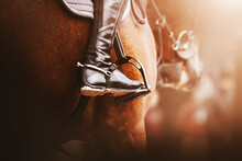 A Rider In Black Boots With Spurs Sits On A Bay Racehorse In The Saddle With Stirrups, Illuminated By Sunlight. Equestrian Sports. Horse Riding.