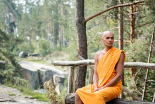 Buddhist Monk In Traditional Orange Robe Sitting On Log Bench In Forest