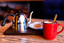 Beautiful Composition Of A Teapot For Tea, A Red Cup And A Saucer With Honey