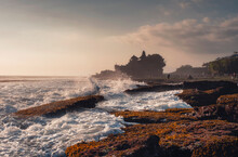 Pura Tanah Lot Temple On Clifftop And Wave Hitting On Sunset Beach In Bali