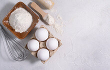 The Flour Is In A Wooden Bowl, The Eggs Are Lying On A Bright Table. Rolling Pin And Whisk In The Background. Space For Text