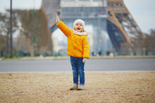Adorable Preschooler Girl In Yellow Jacket Near The Eiffel Tower In Paris