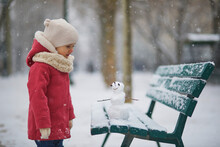 Adorable Toddler Girl Building A Snowman On A Day With Heavy Snowfall