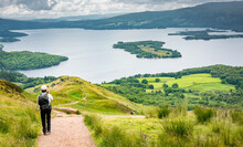 A View Of Loch Lomond From The West Highland Way In Scotland. A Hiker Walking On The Path Down To The Lake.