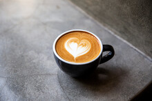 Black Cup Of Cappuccino With Latte Art Of Heart Shape On Saucer On Concrete Background.