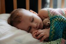 Cute Baby Sleeps Peacefully In Crib With Handle Under His Cheek