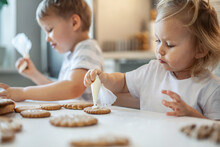 Children Decorate Christmas Gingerbread At Home. A Boy And A Girl Paint With Cornets With Sugar Icing On Cookies. New Year's Decor, Branches Of A Christmas Tree.