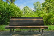 A Wooden Bench Stands In The Shade Of Trees Against The Background Of A Summer Blue Sky And Bright Green Foliage, Shallow Depth Of Field