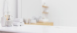 White table top with toiletries over blurred modern bright white bathroom