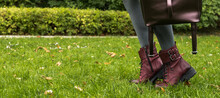 Close-up Of Female Legs In Grey Tights And Skirt. Feet On Tiptoes. Stylish Burgundy Boots. Leather Bag In The Arm. Green Grass. Autumn Fashion.