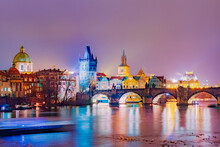 Cityscape View Of Charles Arch Bridge Architecture Accros The River Vltava At Night, In Prague