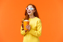Girl Eating Popcorn, Smiling Amused As Staring At Large Screen Watching Movie At Cinema, Open Mouth Thrilled, Wear 3d Glasses On Fantasy Film Theatre, Standing Orange Background