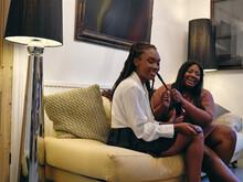 Women Braiding Friends Hair In Living Room