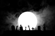 Halloween. Cemetery With Graves And The Dead Stretch Their Hands Up Against The Background Of The Moon With Fog