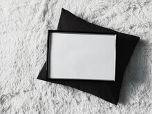 Thin Wooden Frame With Blank Copyspace As Poster Photo Print Mockup, Black Cushion Pillow And Fluffy White Blanket, Flat Lay Background And Art Product, Top View