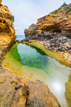 A Still Green Rock Pool At The Base Of A Rocky Sandstone Canyon At The Coast