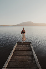 Young Woman Standing At The End Of A Jetty Looking Over A Lake With A Mountain In The Background.