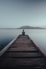 Man Sitting On The End Of A Jetty Looking Over A Lake With A Mountain In The Background.