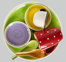 Clean Different Cups Laying On A Large Green Plate With Spoons Isolated On A Light Gray