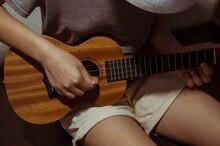 Girl Playing Ukulele Bent Over, Close-up