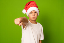 Portrait Of A Serious Boy In A Red Hat And White T-shirt Pointing Finger To Camera On A Green Background. A Child In A Christmas Hat Of Santa Claus.