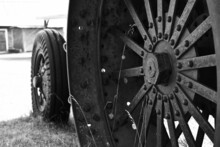 An Image Of An Old Rusted Metal Tractor Tire On Vintage Farming Equipment.