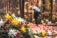Flowers At Tombstone. Defocused Mourning Woman Holding Flowers In Hands And Standing At Grave In Cemetery. Paying Respect And Last Goodbye For Dead Person