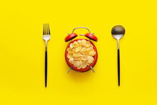 Alarm Clock Fulled With Flakes, Spoon And Fork On Yellow Background