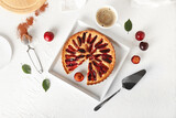 Tray with tasty plum pie and cup of coffee on light background