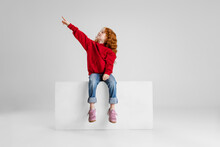 Portrait Of Little Red-haired Curly Girl, Child Pointing Somewhere Isolated Over Gray Studio Background.