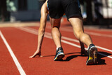 Cropped image of male athlete, runner training at public stadium, sport court or running track outdoors. Summer sport games. Man's legs