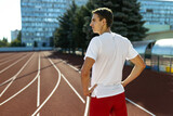 Back view of young Caucasian man, male athlete, runner posing at public stadium, sport court or running track outdoors. Summer sport games.