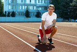 Young Caucasian sportive man, male athlete, runner practicing alone at public stadium, sport court or running track outdoors. Summer sport games.