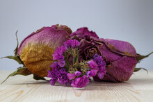 Flower Arrangement Of Dried Flowers On A Wooden Table On A White Background. Rosebuds And Purple Statice, Limonium