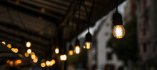 Illumination Of The Street Terrace Of A Cafe Or Restaurant. Light Bulbs. Cloudy Weather.