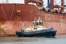 Southampton, England, UK, 2021. Powerful Tub Assisting A Bulk Carrier Ship To Get Alongside In Port