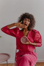 Young African Woman Yawns Covering Her Mouth With Her Palm While Sitting On Chair On White-lilac Background. She Holds Her Desk Clock In Front Of Her, Hinting That It's Time To Sleep.