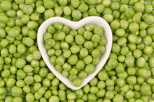Green Peas Are Lying In A White Plate In The Shape Of A Heart On A Background Of Peas.Cultivation And Care Of Agriculture,agronomy, Breeding, Vegetarianism,protein Production,sports Nutrition.