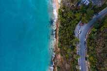 Aerial View Of A Blue Beach And A Highway Amid Dense Green Trees