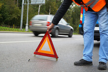 A Man In An Orange Vest Places An Emergency Stop Sign On The Road In Front Of A Faulty Car.