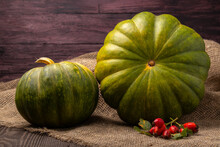 Two Green Pumpkins On A Wooden Table