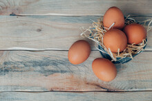 Chicken Eggs On Decorative Straw In A Basin On A Wooden Table.