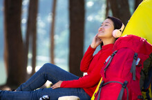 A Young Girl Sits Next To A Camping Tent And A Red Backpack, She Enjoy Listening To Music From Pink Headphones In The Middle Of A Pine Forest Beside The Lake, Pang Oung, Mae Hong Son, Thailand.